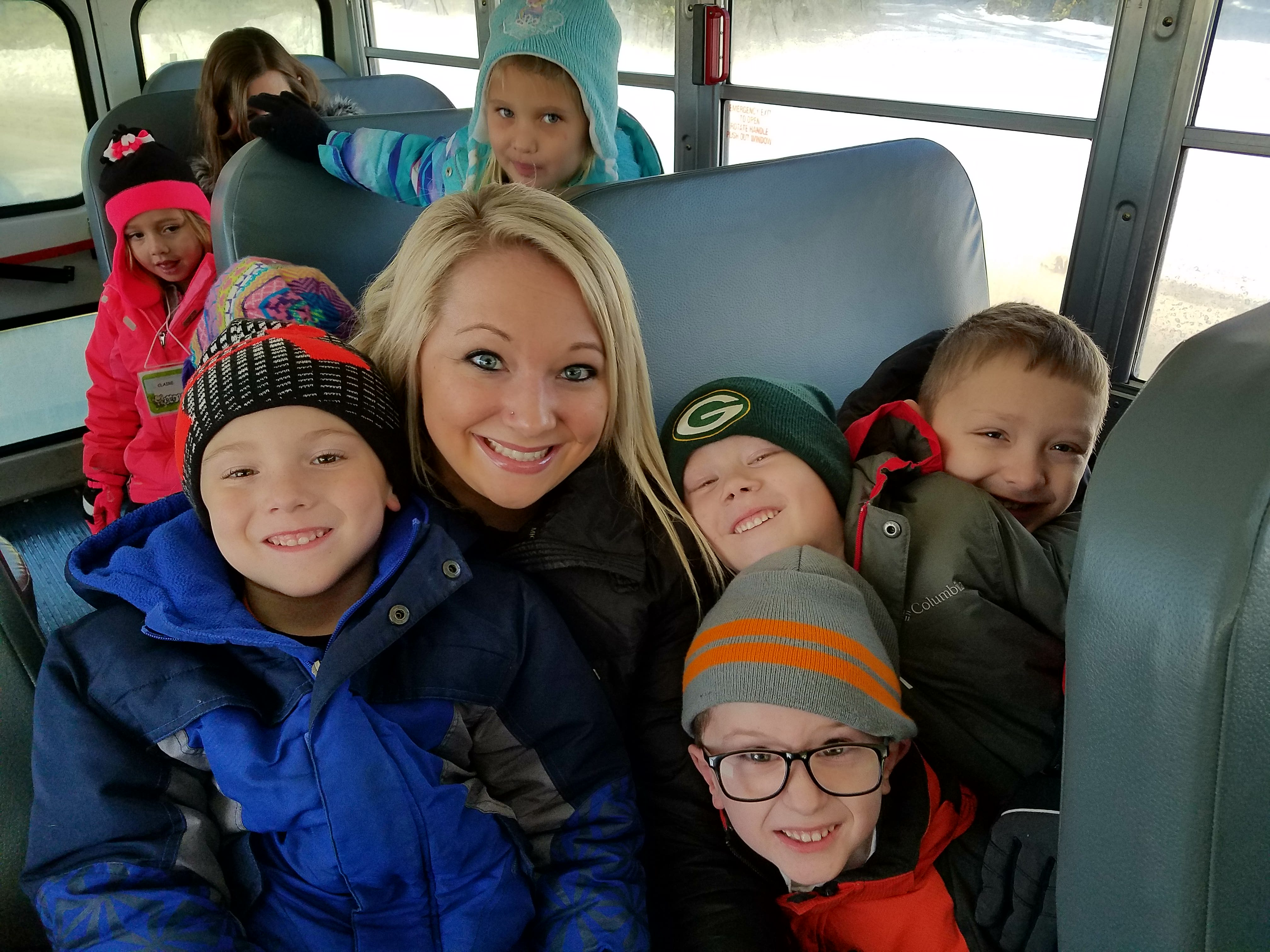 Kindergarten teacher with kids on the bus