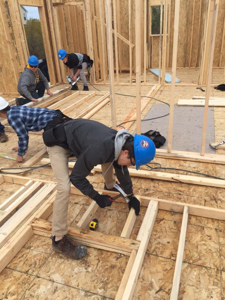 Four students with hard hats on working on the wood framing for the Knight Construction house.