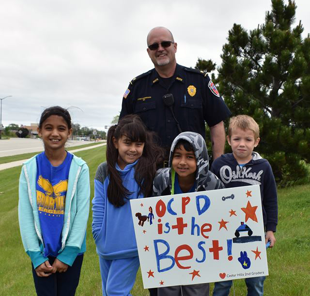 "Students hold ""OCPD is the best"" sign with a police officer"